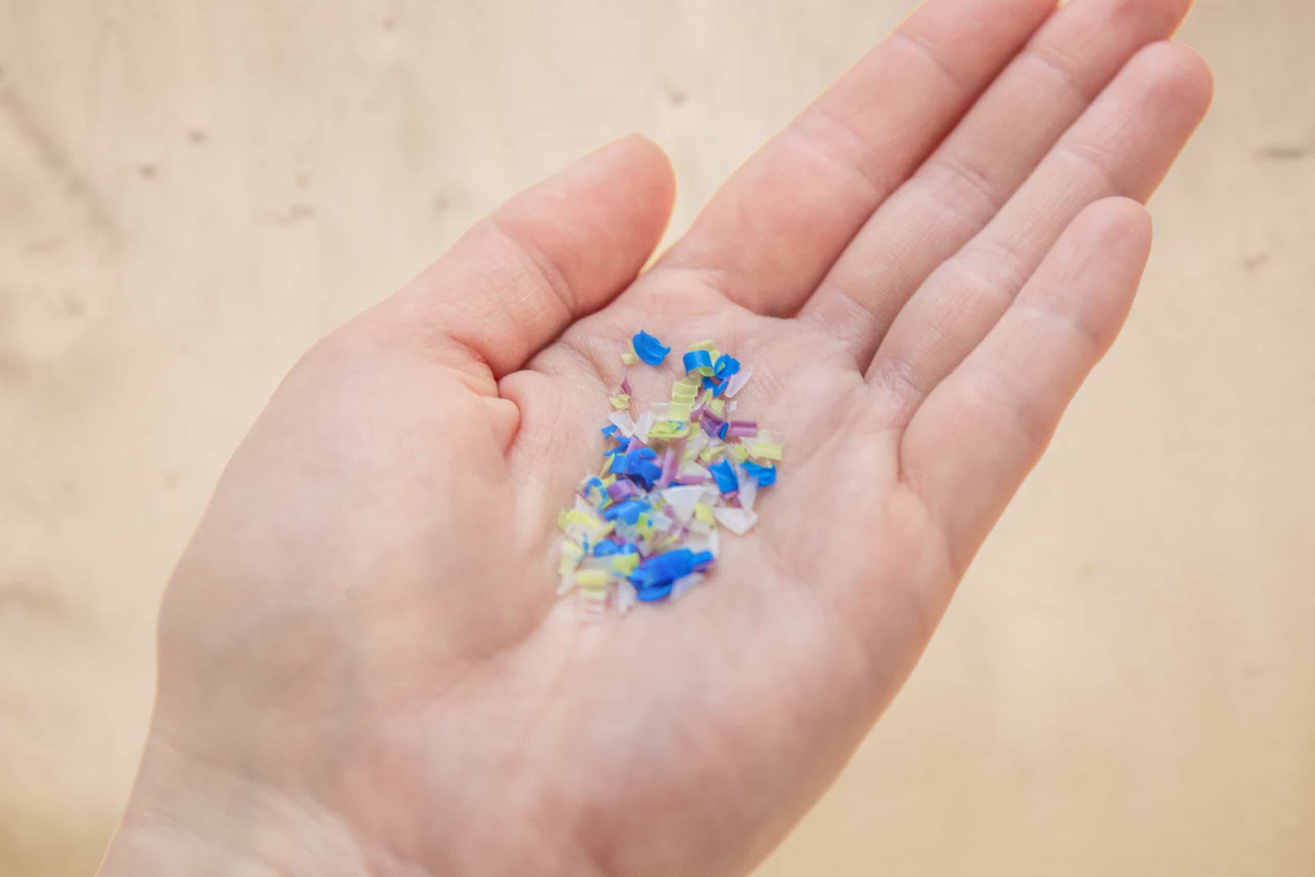 Mikroplastik in der Hand eines Mannes auf dem Strand.