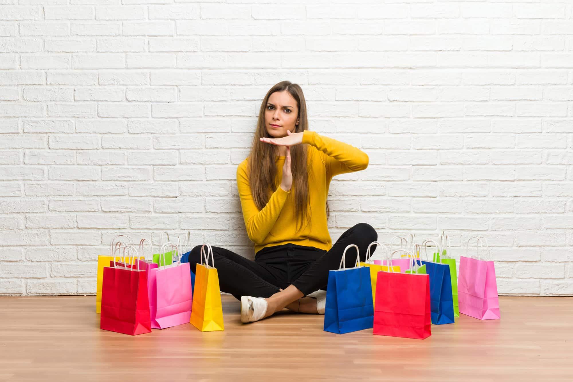 Eine Frau sitzt mit vielen Shopping Taschen um sich herum und zeigt mit der Hand ein Stopp Zeichen.