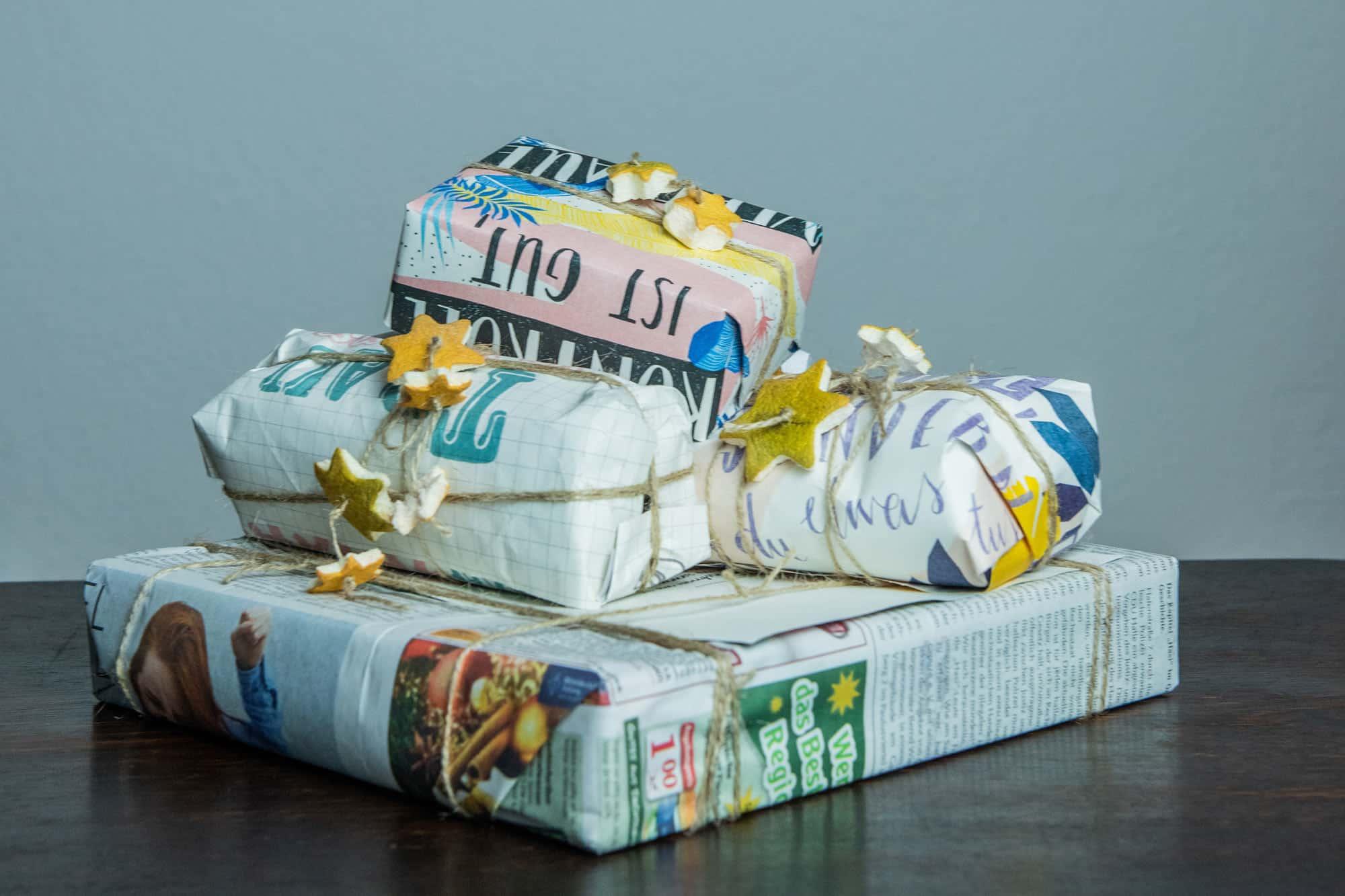 Geschenke in Zeitungspapier eingepackt und mit Sternen aus Orangenschalen geschmückt.