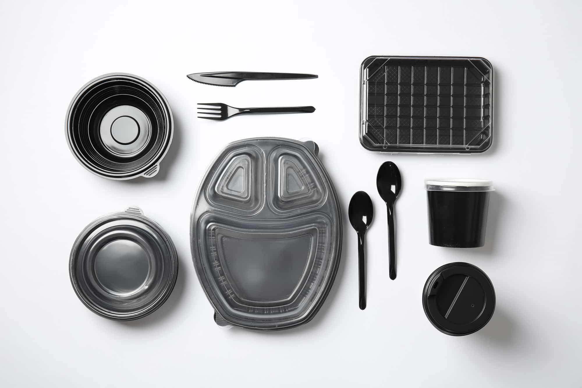 Verpackungen, wie Besteck und To-Go-Becher, aus schwarzem Plastik