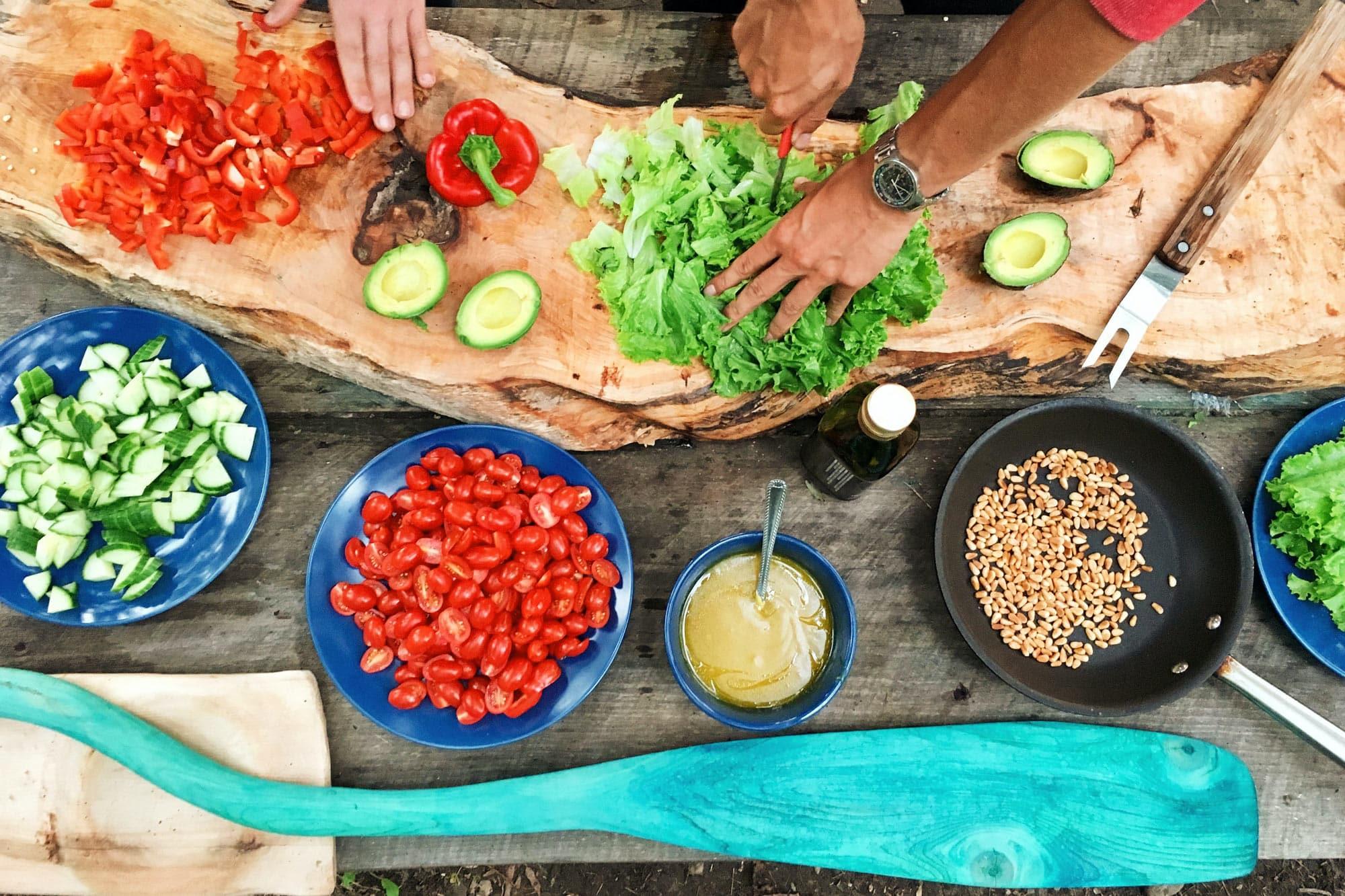 Auf einem Holztisch liegt viel geschnittenes Gemüse, wie Tomaten und Gurken. Dabei werden von zwei Paar Hände noch Paprika und Salat klein geschnitten.