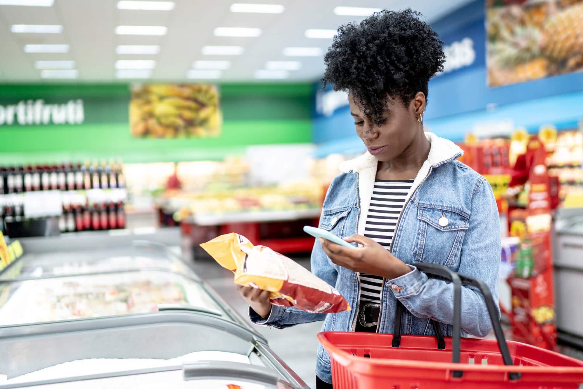 Eine Frau scannt mit ihrem Handy im Supermarkt die Rückseite einer Verpackung.