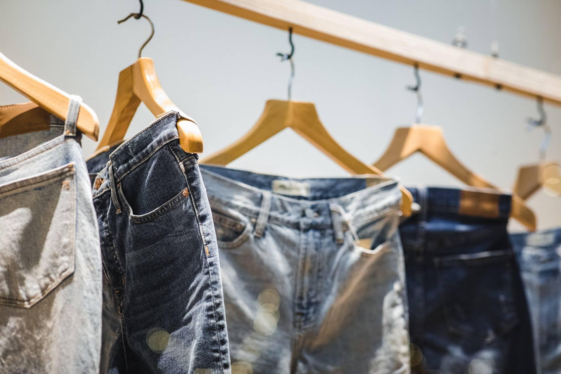 Fünf Jeans hängen an einer Stange in einem Laden.