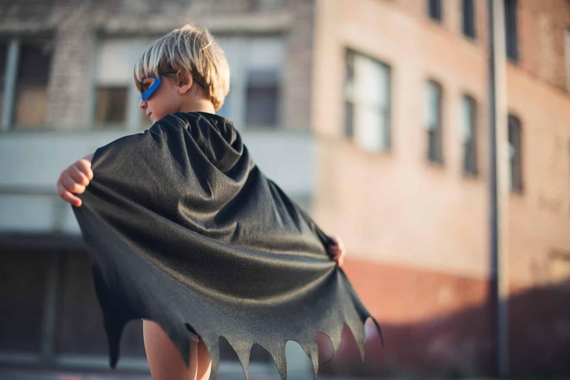 Ein kleiner Junge hat ein Halloween Kostüm an. Er hat die Arme weit ausgebreitet und man sieht den Batman Umhang.