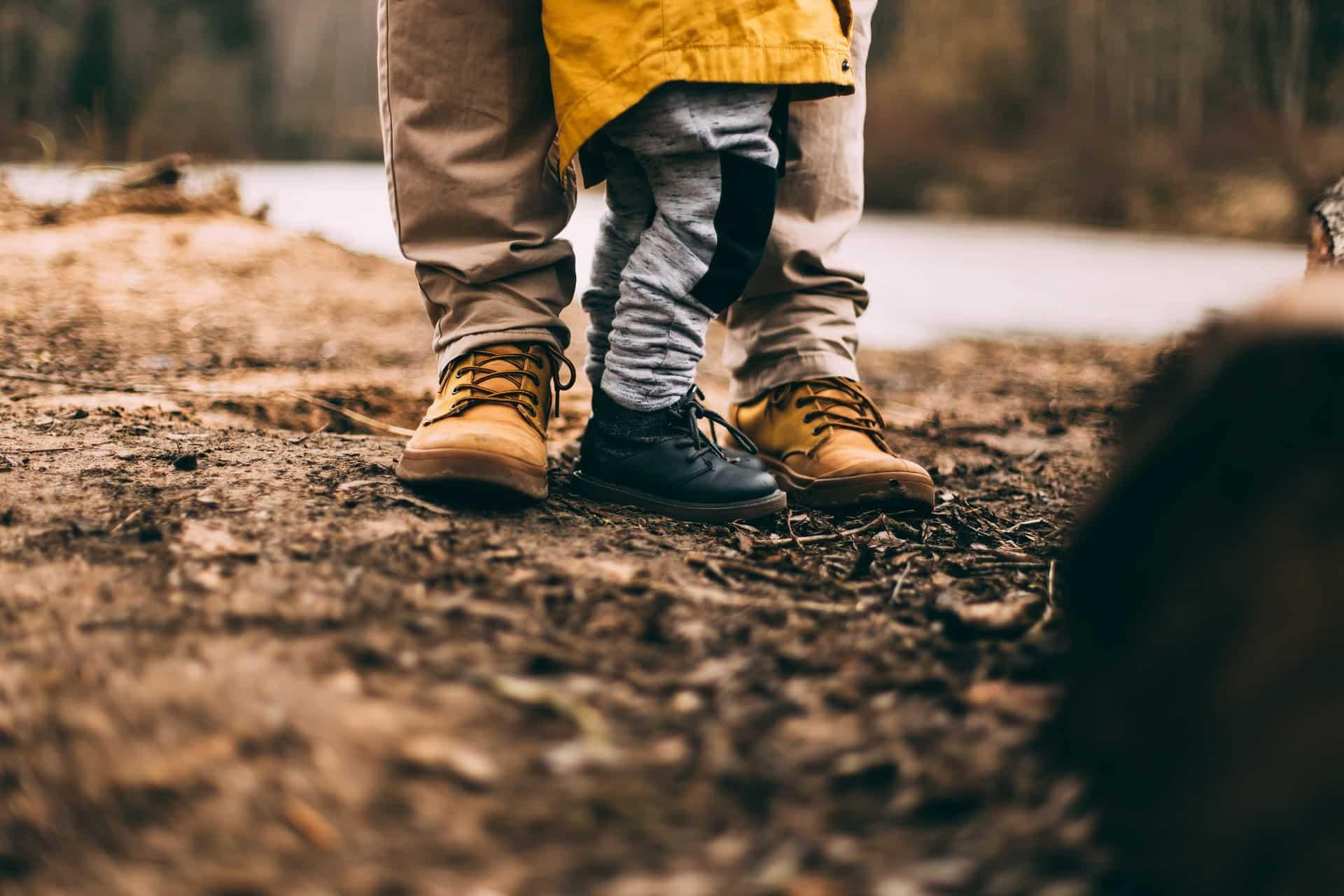 Auf dem Bild sieht man die Beine und Füße von einem Mann und einem Kind. Beide haben Schuhe aus Leder an.